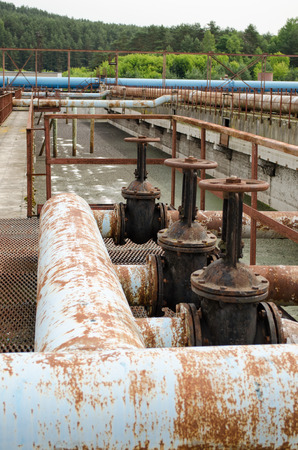 Rusty taps valves gate and pipes in water treatment plant and dirty liquid bubble.  Stock Photo