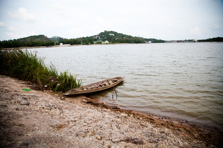 water s edge: old row boat in lake on shore Asia Stock Photo