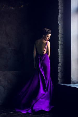a young girl standing near a window in purple long dress