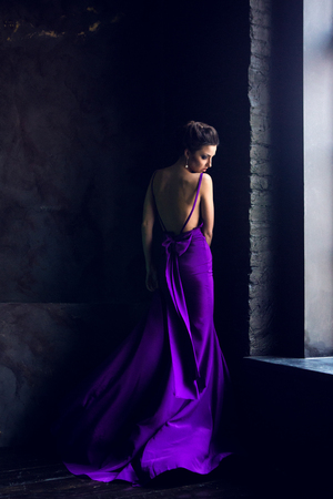 a young girl standing near a window in purple long dress