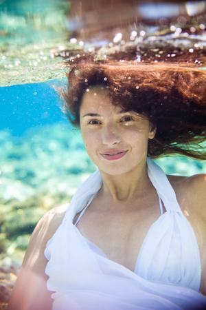 portrait d'une jeune fille aux cheveux longs sous l'eau dans la mer, dans une robe blanche