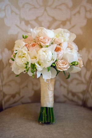 nuance: wedding bouquet of peonies lying on the chair
