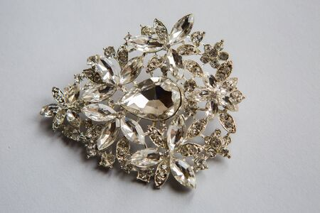 diamond stones: silver brooch in the shape  made of clear stones on a white background Stock Photo