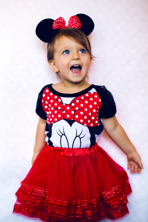 mickey: happy baby in the Studio in a red dress with Mickey mouse ears and mouse