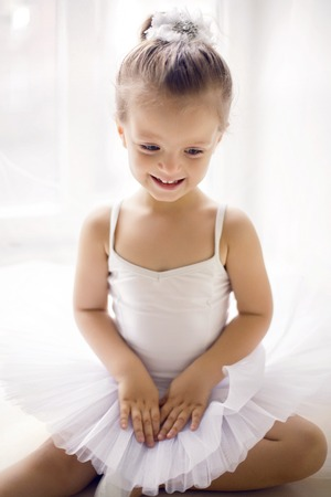 little ballerina girl 2 years in the Studio in a white tutu dress clothes Stock Photo