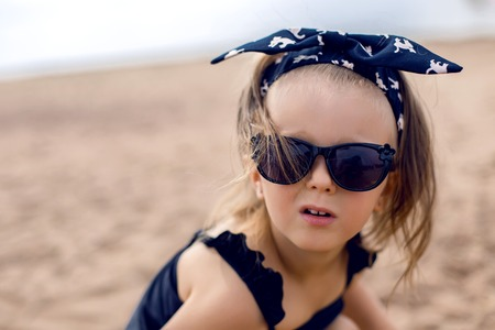 girls bathing: a little girl stands on the shore of the beach in a black bathing suit and black glasses Stock Photo
