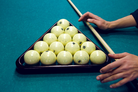cue: white balls for Billiards in a triangle and hands of men and with the cue