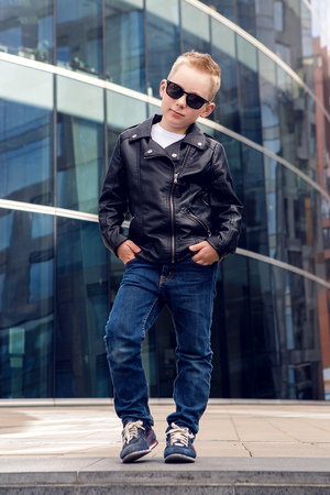 7 8: baby boy 7 - 8 years in sunglasses and black leather jacket smiling on the background of the glass building in the summer, in warm weather