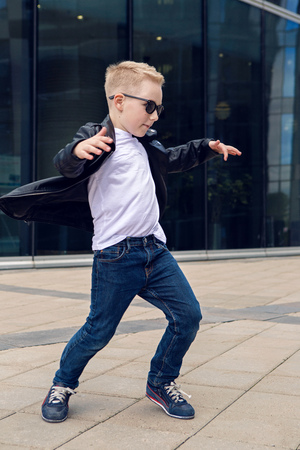 7 8: baby boy 7 - 8 years in a black leather jacket dancing in the street on the background of the glass building in the summer, in warm weather Stock Photo