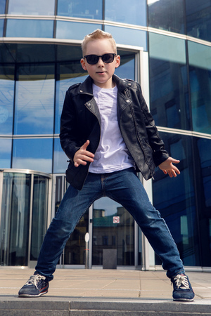 7 8 years: baby boy 7 - 8 years in a black leather jacket dancing in the street on the background of the glass building in the summer, in warm weather Stock Photo