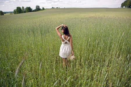 tall and short: young girl with long dark hair, goes on the green field with tall grass with his face to the camera in a short white dress and straw hat Stock Photo
