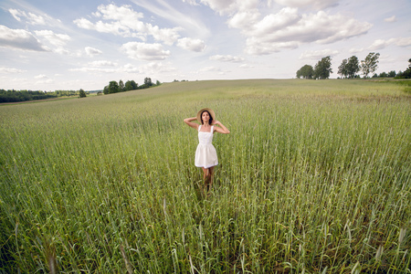goes: young girl with long dark hair, goes on the green field with tall grass with his face to the camera in a short white dress and straw hat Stock Photo