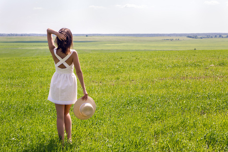 backs: young girl with long dark hair standing on a green field with green grass backs to the camera in a short white summer dress and straw hat and then removes it. throws up his hands and enjoying nature. in the right corner of the screen