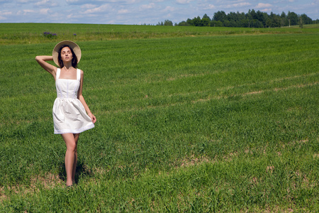 goes: young girl in white dress and holding a straw hat is on the green field with grass and smiles, summer. the model goes on camera