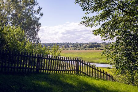 blanketed: old wooden fence in summer Sunny day, covered with moss from time to time Stock Photo
