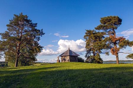 gory: Pushkinskiye Gory, Russia - June 5 : Wooden chapel and stone cross on the top of Savkin hill, Pushkinskiye Gory Reserve, Russia . Birthday of the great writer Alexander Pushkin , on June 5, 2016.