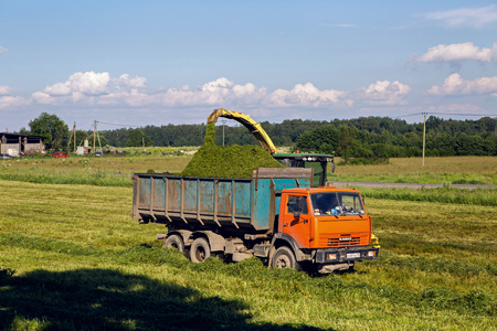 mows: Pushkin, Russia - 2 July : on a green field in the summer of truck driving next to the combine which mows fresh grass in celebration of World UFO Day on 2 July, 2016.