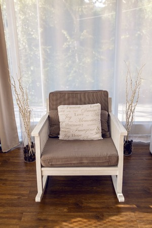 throw cushion: white rocking chair with brown cushion in the interior against white curtains Stock Photo