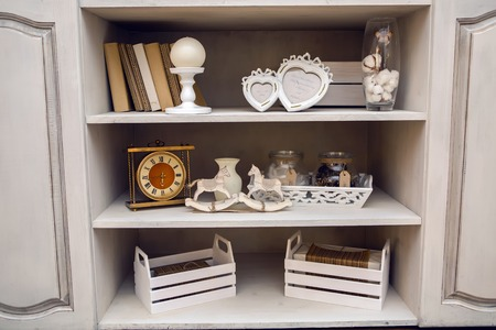 trivia: white outdoor small cupboard with trivia books, clock, wooden horses, jars, candle holders, photo frames Stock Photo
