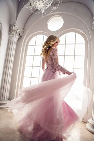 slow motion: beautiful young girl in pink lace dress spinning in the white room