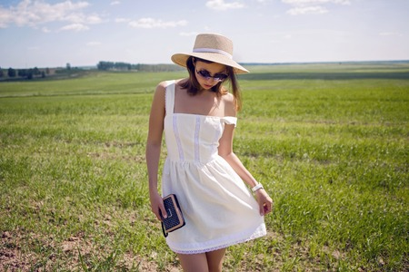 young girl with long black hair stands on the site in white dress and clothes straw hat is on the green field with grass and smiles, summer.
