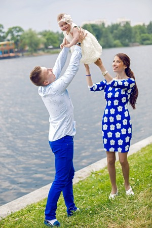 raises: happy young couple raises in the hands of a child girl water. the girl in the blue dress, boy shirt in marine style