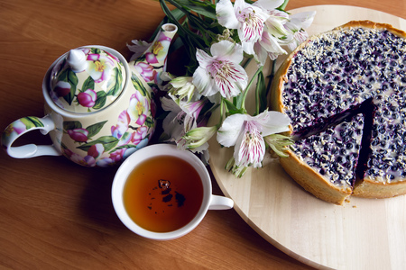 stand teapot: pie from fresh blueberries sprinkled with coconut and standing on a wooden stand, standing next to a porcelain teapot with white Cup tea with flowers