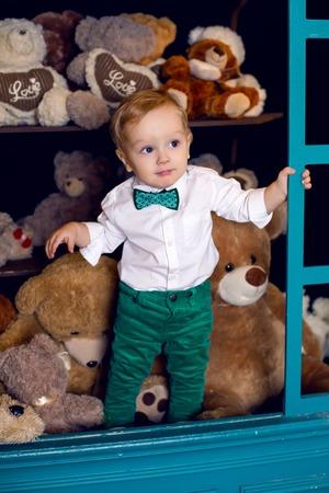 osos navideños: niño pequeño que se coloca en el suelo cerca de los osos de Navidad en la camisa blanca y pantalón verde y corbata