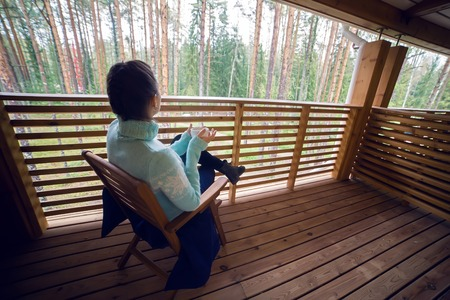 second floor: girl in a blue sweater sitting on a wooden chair and drinking tea from a white mug on the veranda of the second floor balcony in the house in the pine forest.