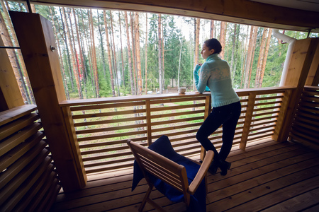 second floor: girl in a blue sweater stand and drinking teafrom a white mug on the veranda of the second floor balcony in the house in the pine forest.