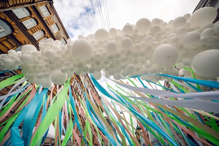 fastened: lot of white balloons fastened together into one and colorful long ribbons at the festival