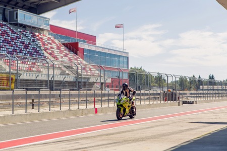 moto gp: Moscow region, Russia - 27 August : route Moscow raceway motorcycle racer in a green suit and helmet, riding a motorcycle around the pits to practice in day of Russian cinema 27 August, 2016.