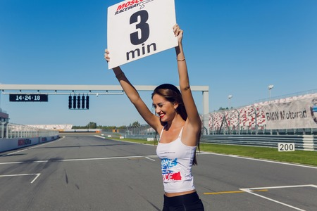 shootings: Moscow region, Russia - 27 August : route Moscow raceway girl model with long hair and a white t-shirt bears a sign with the time on the track before the race riders in day of Russian cinema 27 August, 2016.