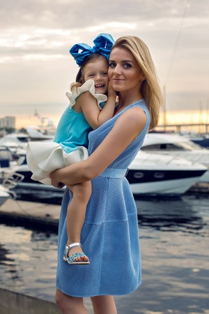 ship bow: little girl three years sitting on my mothers hands with long blond hair and they are dressed in blue dress and large blue bow on her head , sitting at the pier on the sea with a yacht during sunset Stock Photo