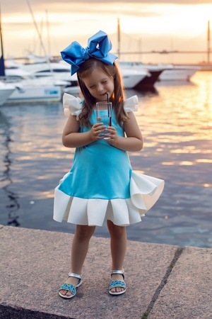 ittle: portrait of a little girl three years with the blue bow on her head, stands near the water and near the dock where there are boats at sunset in the summer, drinking a glass of water through a straw