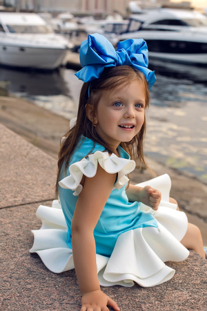 ittle: portrait of a little girl three years with the blue bow on her head, which is smiling and looking forward interested Stock Photo
