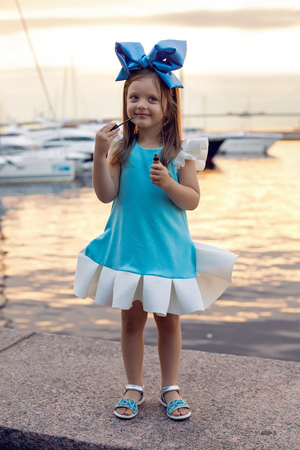 ittle: portrait of a little girl three years with the blue bow on her head, stands near the water and near the dock where there are boats at sunset in the summer, wearing lipstick