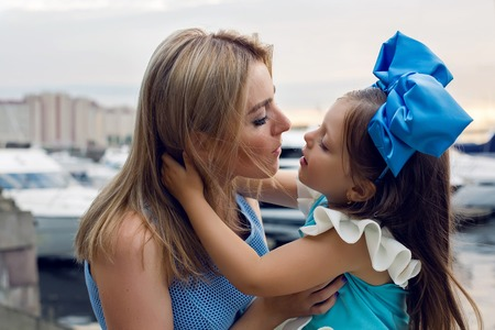 ship bow: little girl three years sitting on the lap of the mother with long blond hair and they are dressed in blue dress and large blue bow on her head , sitting at the pier by the sea with yachts at sunset