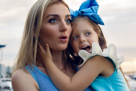 ship bow: little girl three years sitting with mom with long blond hair and they are dressed in blue dress and large blue bow on her head , sitting at the pier on the sea with a yacht during sunset