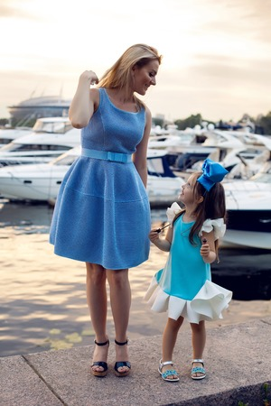 ittle: portrait of a little girl three years with the blue bow on her head, stands near the water and near the dock where there are boats at sunset in the summer, wearing lipstick my mom