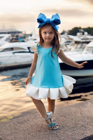 ittle: portrait of a little girl three years with the blue bow on her head, stands near the water and near the dock where there are boats at sunset in the summer