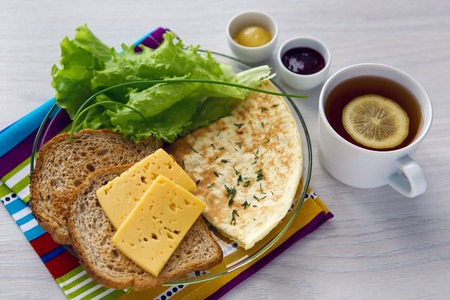 scrambled: Breakfast with scrambled eggs on a transparent plate with toast, lettuce, tea with lemon , honey and raspberry jam Stock Photo
