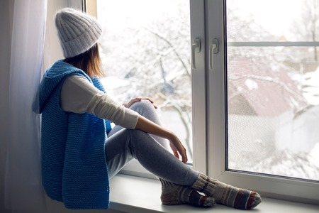 girl in a white hat and blue vest is sitting on the windowsill Stock Photo