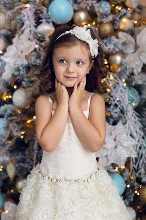 ca97d27fdd #66226400 - Niña de tres años en un vestido blanco sonriendo en el árbol de  Navidad decorado en la habitación