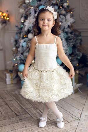 af37cff1c8 #66226398 - Niña de tres años de edad en un vestido blanco que sonríe en el  árbol de Navidad decorado en la habitación
