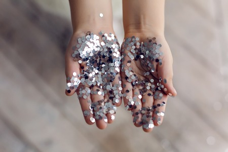 hands of a little girl holding silver sequins