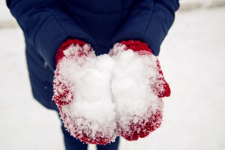etched: hands in red mittens holding snow in the street
