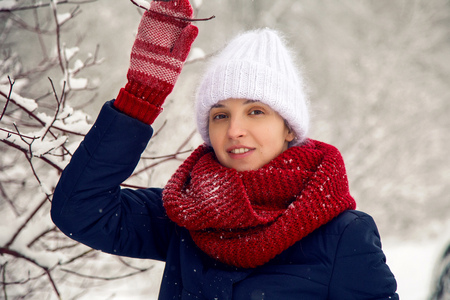 smiling girl in a knitted red scarf, white knitted hat and red mittens stands at the trees in the snowy forest