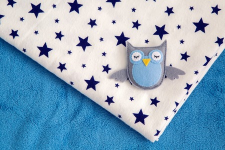 toy owl rests on a childs diaper with stars Banque d'images