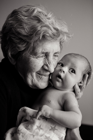 증조 할머니는 그의 사랑하는 손자 손을 창 옆에두고있다. 스톡 콘텐츠